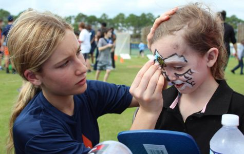 Sofia Abbonizio paints a student's face during the Friendship Games.