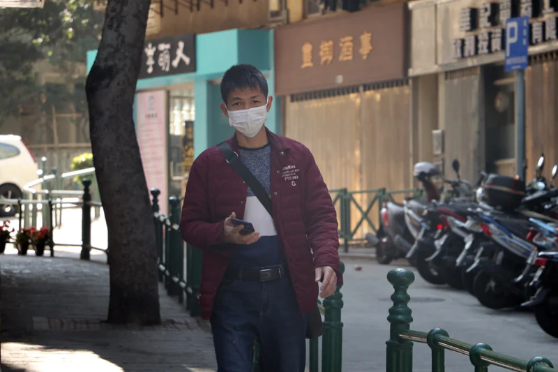 A man walks in Macau, China, wearing a mask to protect him from the virus.