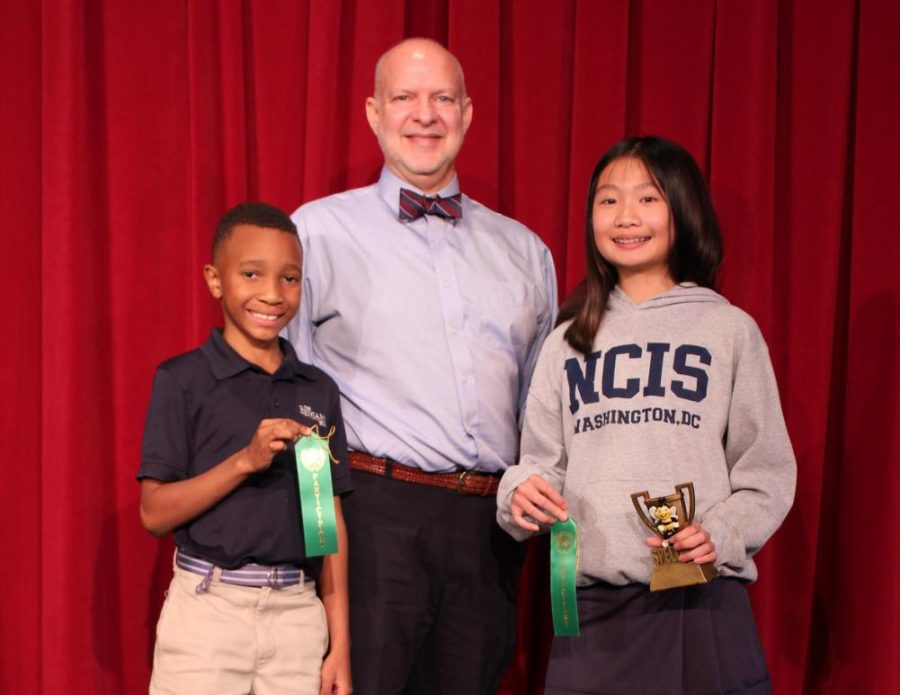 Claire Dinh (right) and Ishe Makoni stand on the stage with Mr. Hagy after the spelling bee.