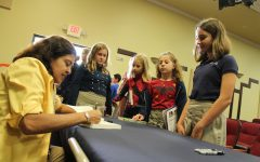 Ms. Perkins signs one of her books for sixth grader Sage Ponchock after her presentation in the BPAC.