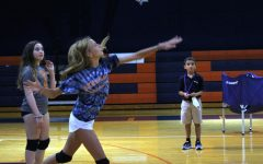 With teammate Treasure Stein watching, seventh grader Addison Walczak strikes the ball over the net during volleyball practice.