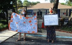 Mrs. Andrea Dumont and Mrs. Chrissie Ferguson welcome sixth graders with signs during the drive by