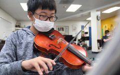 Seventh grader Han Tang practices a piece on his violin in Mr. Winter