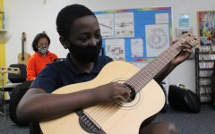 Sixth grader Jayden Jean-Baptiste plucks his guitar during Mr. Huber's E-period band class.