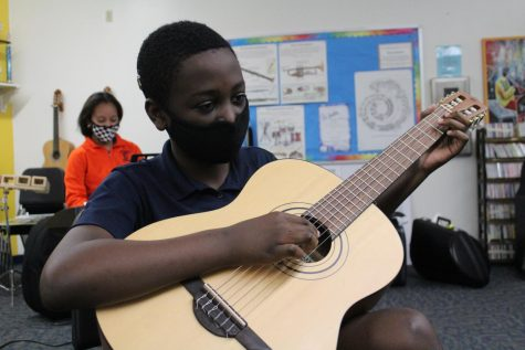 Sixth grader Jayden Jean-Baptiste plucks his guitar during Mr. Huber