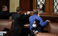 Capitol Police draw their guns on a crowd of people attempting to break into the House chamber.