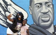 Standing in front of a mural honoring George Floyd in Houston, Margaret Williams, takes a picture with her daughter, Nala.