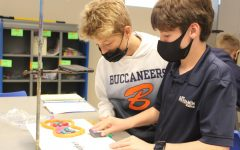Seventh graders Jackson Hill and Carter Burden erase some text from their whiteboard in order to take the next photo of their mitosis illustration.