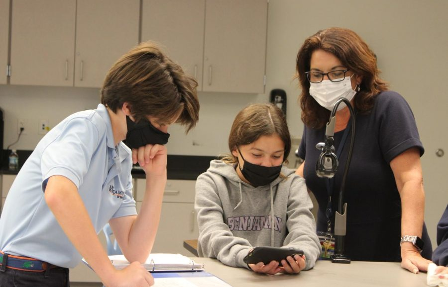 Mrs. Oster looks over the  animation of seventh grader Kenna Kujawa while James Carpenter works on his project nearby.