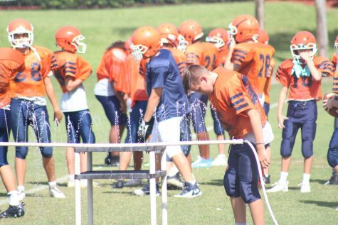 Seventh grader Declan Zinkil cools off from practice during  a break in the action on August 30.