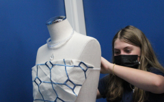 Eighth grader Abbey Trousdale puts the finishing touches on the outfit she designed in Ms. McAllisters visual art class.